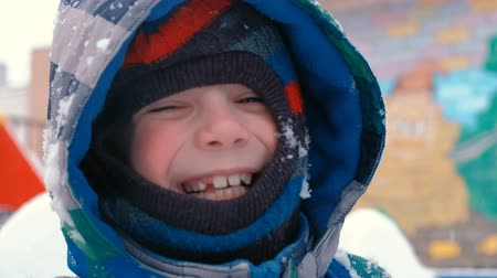 Happy boy in winter clothes smiling looking at camera during snowfall.