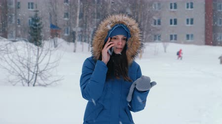 Young beautiful woman talking on the phone outdoors in the winter snowfall.