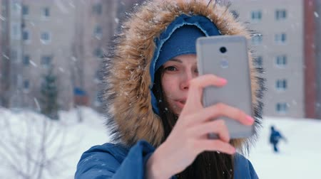Young beautiful woman talking on video on the mobile phone in winter.