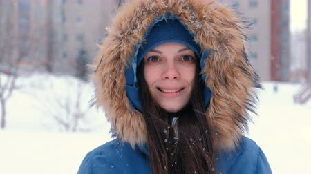 Young woman brunette looking at camera and smiling. Wearing blue down jacket with fur hood, face close-up. Wideo