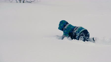 Boy jumps snow drifts, crawls and digs in the snow.