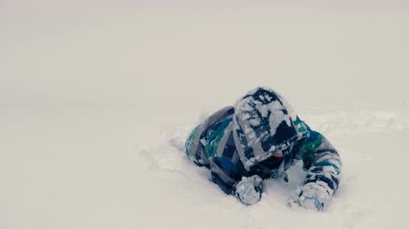 Boy plays in snow drifts in winter. Crawls and digs in the snow. Wideo