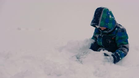 pálido : Boy digs a hole in the snow and sits down in it.
