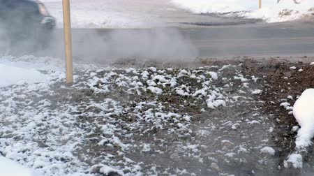 Steam goes near the roadway in winter. Cars drive on the road. Side view. Wideo