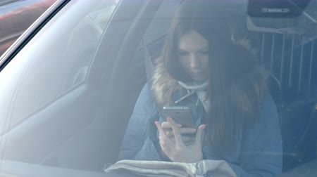 View through windshield of the car on young brunette woman in blue down jacket looking at the phone.