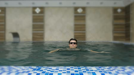 Man swims in the pool in sunglasses.
