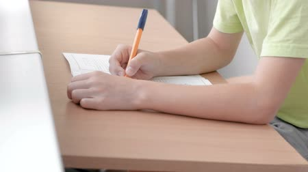 small pen : School child learns to write letters sitting by the table. Close-up boys hands.