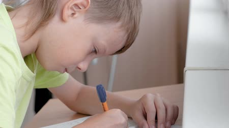 School child boy learns to write letters sitting by the table. Doing homework. Wideo