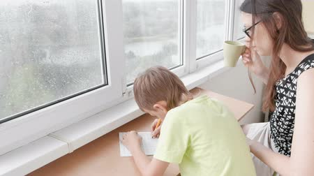 Boy learns to write letters sitting by the table. Doing homework with his mom.