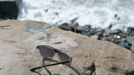Sunglasses on the stone by the sea.