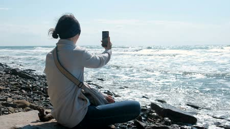 Woman makes selfie sitting by the sea on stone beach in autumn.
