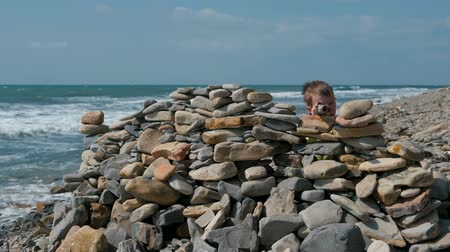 Boy playing, hiding behind a fortress of stones on the sea shore beach.
