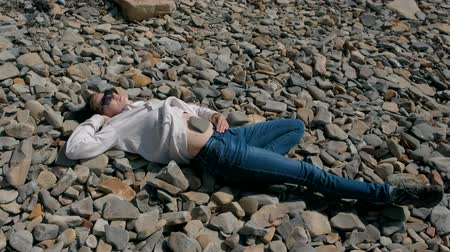 Woman in sunglasses lying on a stone beach in the fall. Stone on the girls belly.