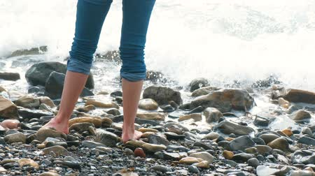kalmak : Woman stands on a stone beach in the waves. Feet in jeans close-up. Stok Video
