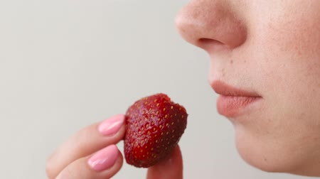 Woman eats strawberries. Mouth close-up. Side view.