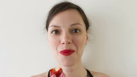 fruity garden : Portrait of woman eating strawberries. Front view.