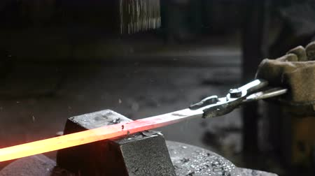 marreta : Making the sword out of metal at the forge. Closeup mans hand using pneumatic hammer to shape hot metal.