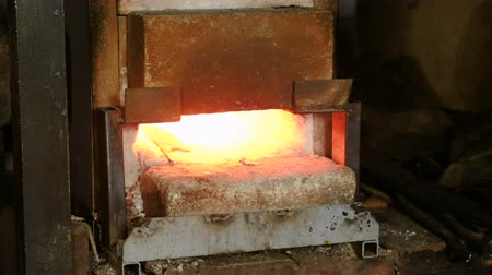 Making the knife out of metal at the forge. Heating of metal billets in the furnace.