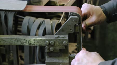 kütük : Grinding billets of metal knife on a belt-grinding machine. Close-up of a mans hand. Stok Video