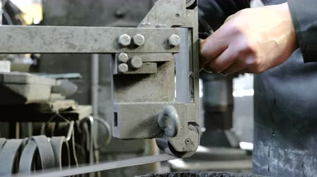 odpowiedzialność : Grinding billets of metal knife on a belt-grinding machine. Close-up of a mans hands.