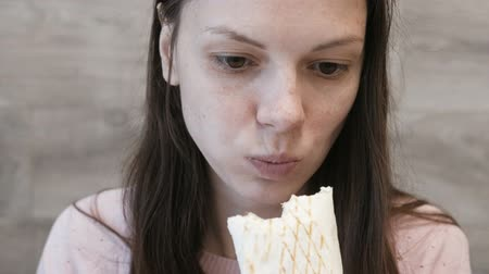 lavash : Young brunette woman eating danar or Shawarma sitting in a cafe.