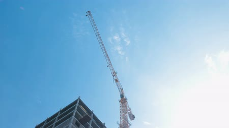 em desenvolvimento : Multi-storey under construction building and construction crane on the background of clear sky.