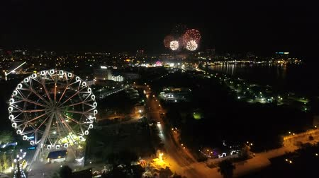 solene : Festive fireworks over a small town on the coast at night. Aerial view of the city, sea, ferris wheel and fireworks.
