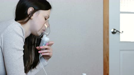 respiratory infection : Use nebulizer and inhaler for the treatment. Young woman inhaling through inhaler mask. Side view. Stock Footage