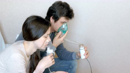 sedative : Use nebulizer and inhaler for the treatment. Man and woman inhaling through inhaler mask. Side view. Stock Footage
