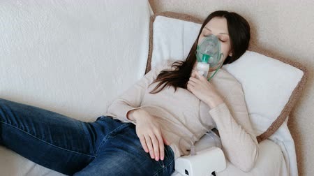 yatıştırıcı : Use nebulizer and inhaler for the treatment. Young woman inhaling through inhaler mask lying on the couch. Front view. Stok Video