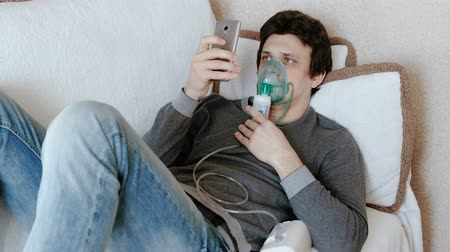 pŁuca : Use nebulizer and inhaler for the treatment. Young man inhaling through inhaler mask lying on the couch and chatting in mobile phone. Side view. Wideo