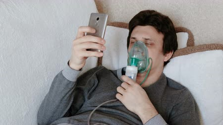 sedative : Use nebulizer and inhaler for the treatment. Young man inhaling through inhaler mask lying on the couch and chatting in mobile phone. Side view. Stock Footage