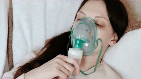 soluma : Use nebulizer and inhaler for the treatment. Young woman inhaling through inhaler mask lying on the couch. Side view. Stok Video