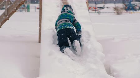 сугроб : Boy crawls on a wooden slide up in the snow during snowfall in the yard of a multi-storey building. Стоковые видеозаписи