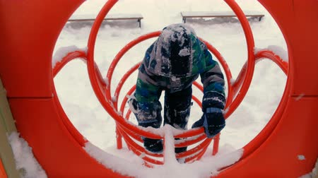 сугроб : Boy plays on playground in winter.