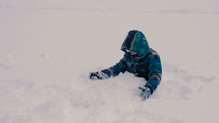 závěj : Boy buries himself in the snow, playing with the snow.