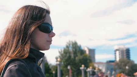 human interest : Young brunette woman in sunglasses on the city background in autumn.