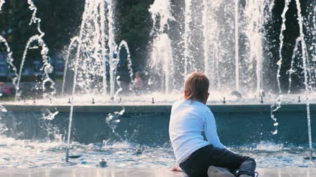 youngsters : Boy looks at fountain in sunny day. Stock Footage