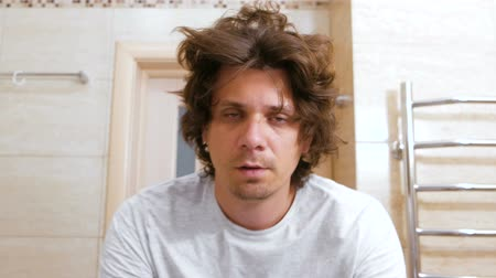 taranmamış : Sleepy shaggy young man looks at the mirror in bathroom in the morning.