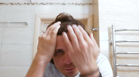 schoonmaken : Sleepy shaggy young man looks at the mirror in bathroom in the morning and combs long hair with hands.