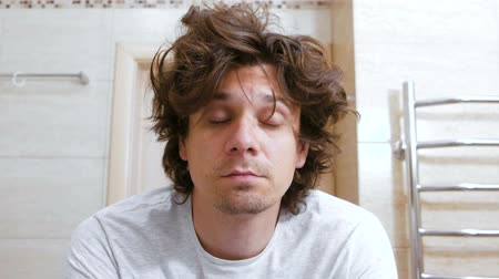 limpar : Sleepy shaggy young man looks at the mirror in bathroom in the morning and surprised.