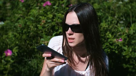 gravador : Beautiful brunette woman records a voice message on her mobile phone while sitting in the park on a Sunny day. Stock Footage