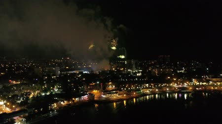 solene : Festive fireworks in a small town on the coast at night. Aerial view of the city, sea and fireworks.