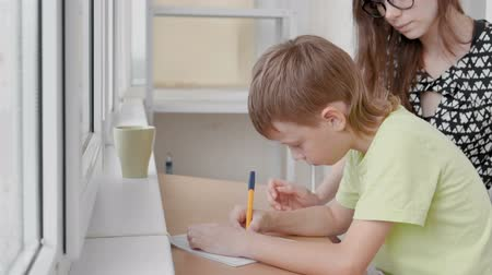 zaměřen : Boy learns to write letters sitting by the table. Doing homework with his mom.