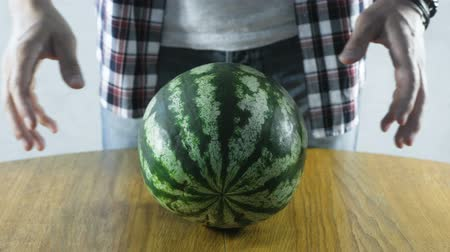 клетчатый : Man puts a watermelon on the kitchen table. Close-up hands.