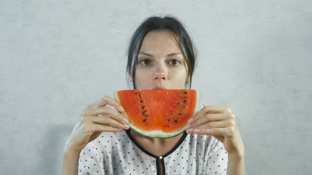 nápadný : Brunette woman eating juicy watermelon on white background. Dostupné videozáznamy