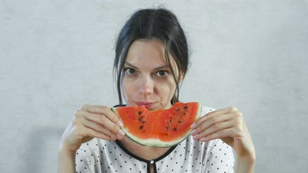 ısırma : Brunette woman eating juicy watermelon on white background. Stok Video