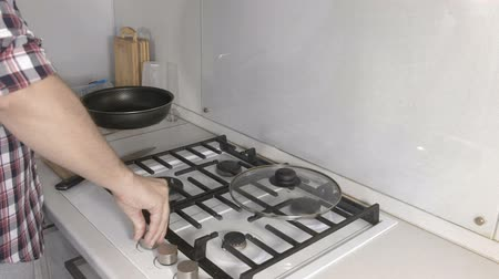 gas stove : Man is frying sausage in a frying pan using sunflower oil. Hads close-up.