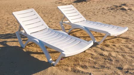 chaise longue : Two sunlongers on the sand beach close-up view. Stock Footage