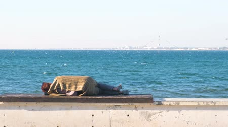 bulutsuz : Homeless woman sleeping on a bench on the sea waterfront.